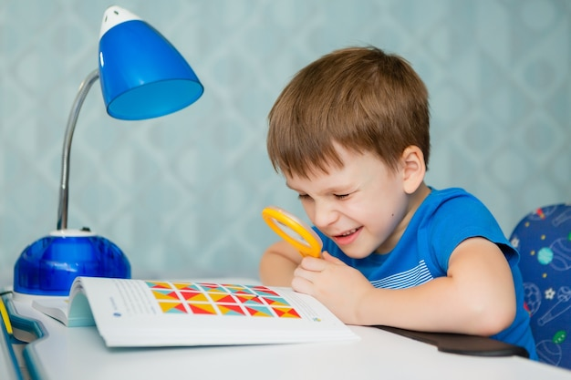 Uczeń chłopiec siedzi przy biurku i uczy się lekcji. w dłoni trzyma lupę