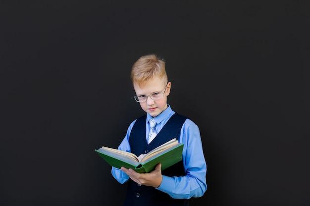 Uczeń czyta książkę na tablicy szkolnej