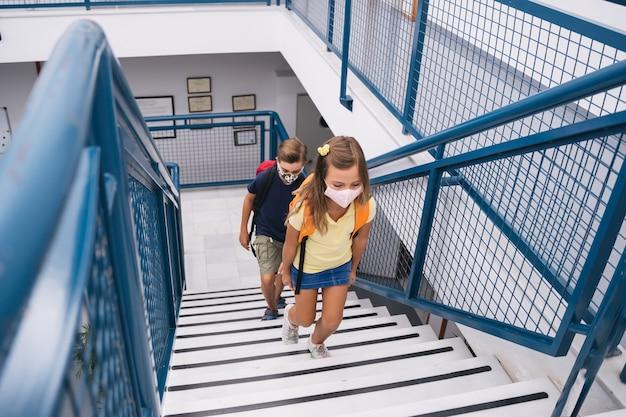 Uczeń dzieci wchodzą po schodach w maskach, aby wejść na zajęcia z zachowaniem dystansu społecznego. powrót do szkoły podczas ukrytej pandemii