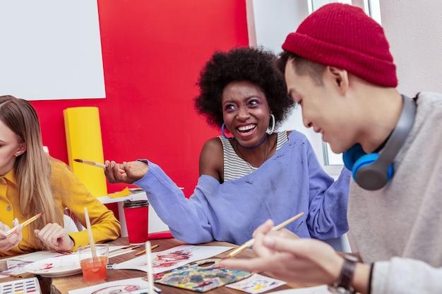 Uczeń emocjonalny. międzynarodowy piękny stylowy student czuje się emocjonalnie rozmawiając z przyjacielem