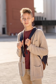 Uczeń gimnazjum w stroju codziennym stojący na zewnątrz