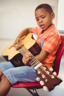 Uczeń gra na gitarze w klasie