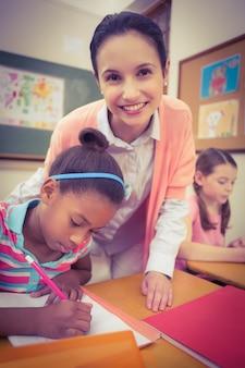 Uczeń i nauczyciel przy biurku w klasie