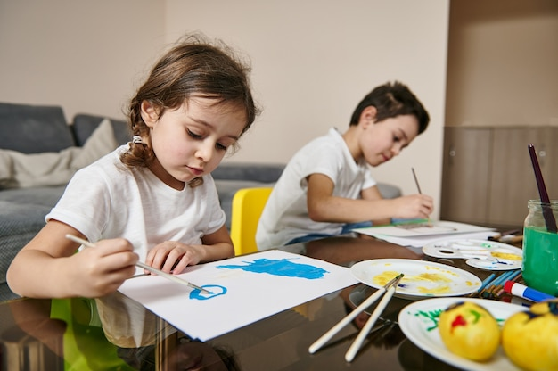 Uczeń i przedszkolak wykonujący technikę malowania akwarelą podczas lekcji kreatywności w pomieszczeniu.