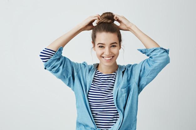 Uczeń jest gotowy, aby rozpocząć pracę nad swoim obrazem. portret piękna szczęśliwa dziewczyna robi fryzurze kok, ciągnie włosy rękami i uśmiecha się szeroko. na stojąco