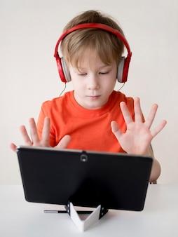 Uczeń liczy palcami i pokazuje do kamery internetowej