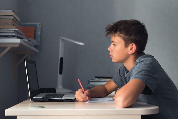 Uczeń nastolatek chłopiec odrabiający pracę domową z laptopem otwarty zeszyt i komputerowe miejsce pracy w domu