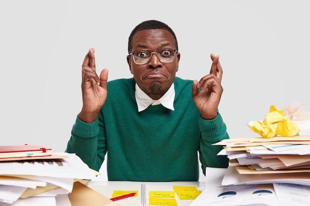 Uczeń o ciemnej karnacji ma żałosny wyraz twarzy, trzyma kciuki, wierzy w szczęście na sesji egzaminacyjnej, przygotowuje projekt z ekonomii