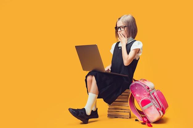 Uczeń pełnej długości w szoku, siedzący na stosie książek, patrzący na koncepcję edukacji dzieci na laptopie