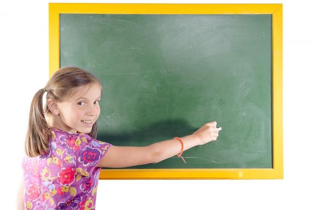 Uczeń pierwszej klasy dziewczynka pisze na zielonej tablicy