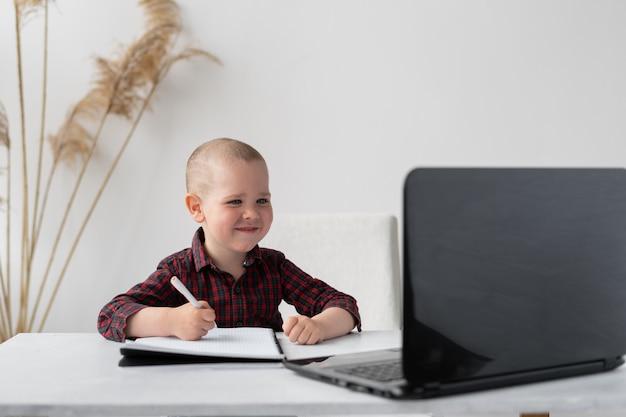 Uczeń pierwszej klasy uczy się zdalnie w kwarantannie. chłopiec siedzi przy stole. uśmiecha się i trzyma w dłoni długopis. jego notatnik na stole i laptop też. edukacja online.