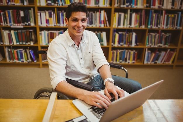 Uczeń pisać na maszynie na jego laptopie w bibliotece w wózku inwalidzkim