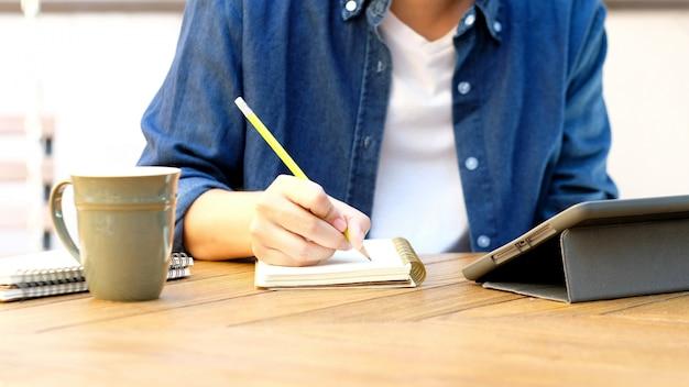 Uczeń pisze na notatniku podczas gdy używać cyfrową pastylkę