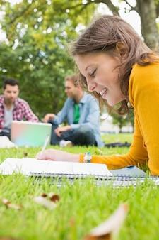 Uczeń pisze notatkach z samiec używa laptop w parku
