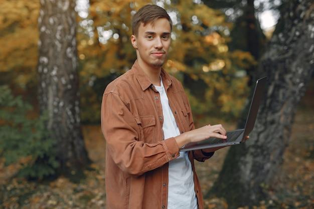 Uczeń pracuje w parku i korzysta z laptopa