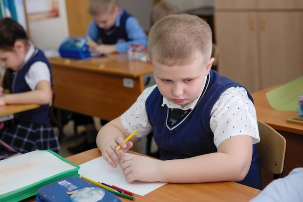 Uczeń przy biurku w klasie podczas lekcji. szkoła podstawowa. selektywna ostrość.
