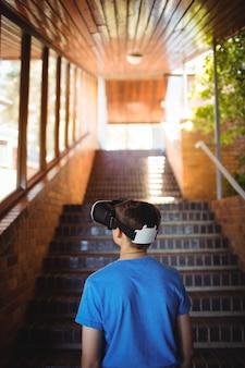 Uczeń przy użyciu zestawu słuchawkowego wirtualnej rzeczywistości na klatce schodowej