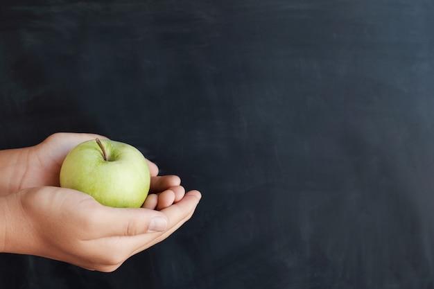 Uczeń ręki trzyma zielonego jabłka z blackboard tłem