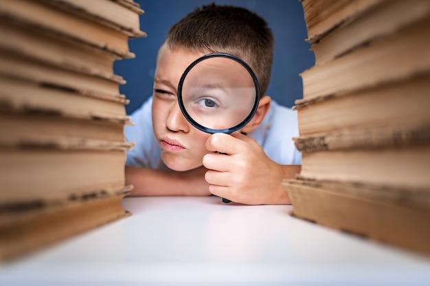 Uczeń siedzi między dwoma stosami książek patrząc na kamery przez szkło powiększające.