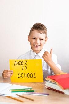 Uczeń siedzi przy biurku z żółtym znakiem powrotu do szkoły i pokazuje kciuk w górę