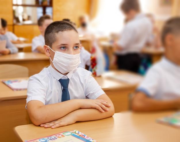 Uczeń siedzi w klasie chłopiec odrabia lekcje przy ławkach w klasie