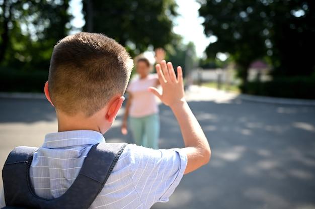 Uczeń stoi przy wejściu do szkoły i macha do swojej zamazanej matki. nieostra matka zabiera syna do szkoły. rozpoczęcie roku szkolnego.