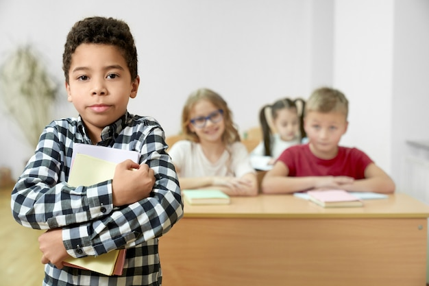 Uczeń stoi w klasie, trzyma książki, pozuje.