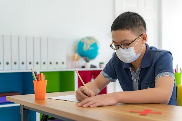 Uczeń szkoły podstawowej nosi maskę higieniczną, aby zapobiec