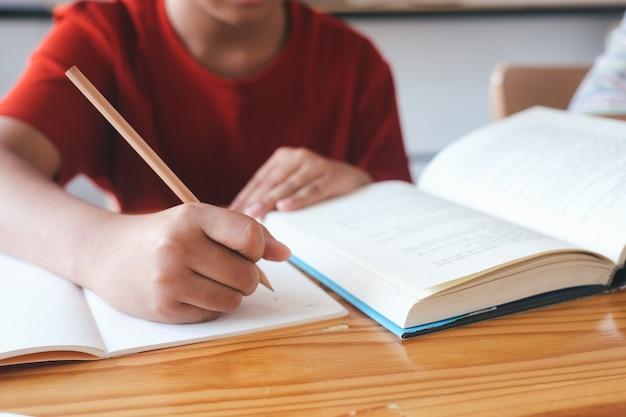 Uczeń szkoły podstawowej uczy się samodzielnie i odrabia prace domowe w domu. edukacja i nauka na odległość dla dzieci. edukacja domowa podczas kwarantanny.