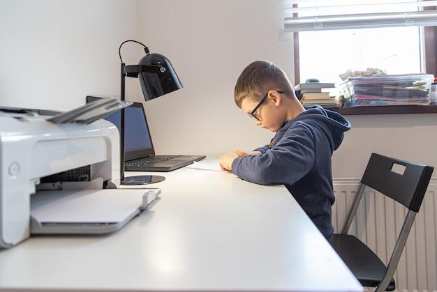 Uczeń szkoły podstawowej uczy się zdalnie w domu, przed laptopem przy biurku.