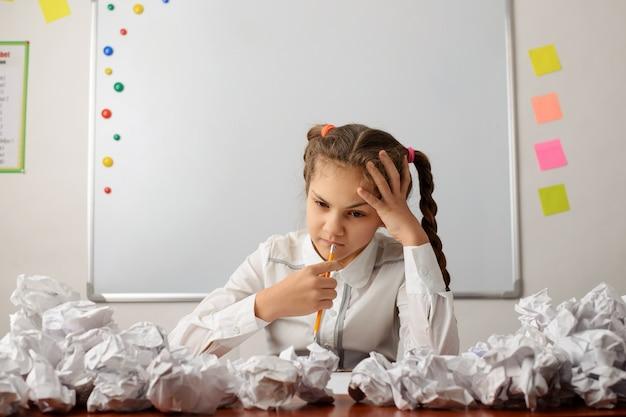 Uczeń szkoły średniej, myślący o jakimś zadaniu, próbuje wykonać zadanie domowe, siedząc przed tablicą z wieloma pomiętymi papierami dookoła