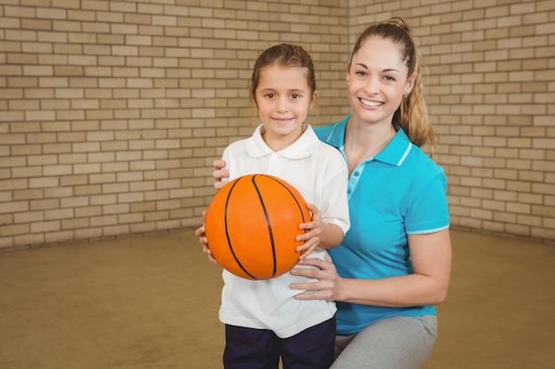 Uczeń trzyma koszykówkę z nauczycielem