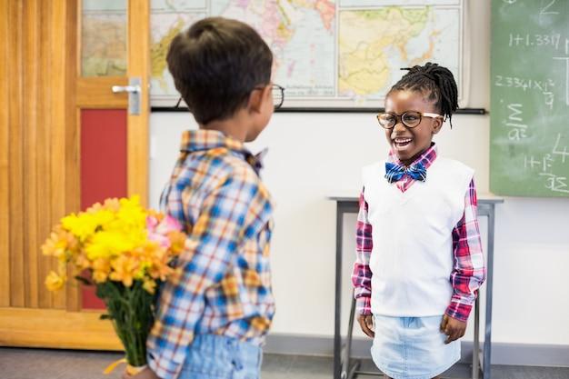 Uczeń ukrywa kwiat za jego plecami w klasie