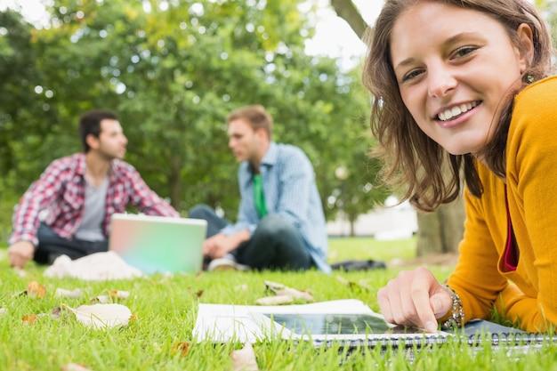 Uczeń używa pastylka peceta podczas gdy samiec używa laptop w parku