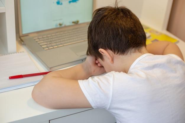 Uczeń w białej koszulce, zmęczony siedzeniem przy monitorze z laptopem i trzymaniem głowy w dłoniach