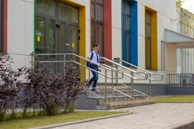 Uczeń w białej koszuli, niebieskim krawacie i plecaku schodzi ze schodów