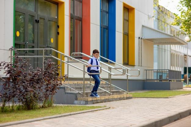 Uczeń w białej koszuli, niebieskim krawacie i plecaku schodzi ze schodów.