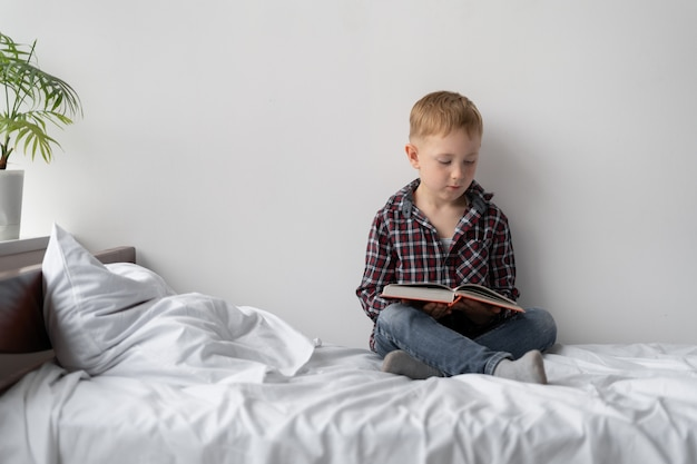 Uczeń w domu w kwarantannie. nauka na odległość. blond chłopiec siedzi na łóżku i czyta książkę. dziecko zostaje w domu i samodzielnie odrabia lekcje. odpocznij od szkoły przed wakacjami.