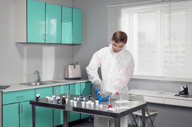 Uczeń w laboratorium. młody chemik mężczyzna pracujący w laboratorium.