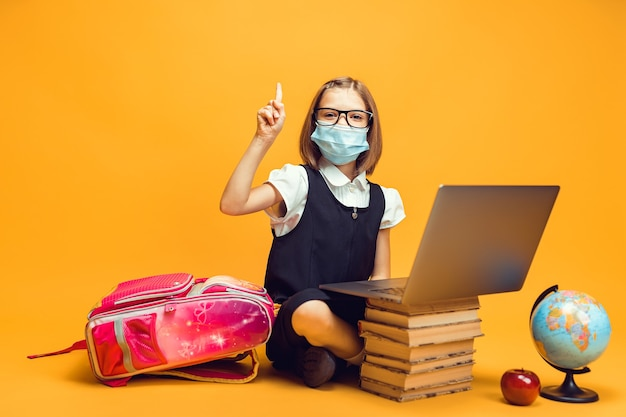 Uczeń w masce medycznej siedzi za stosem książek, a laptop podnosi palec wskazujący w kierunku edukacji dzieci