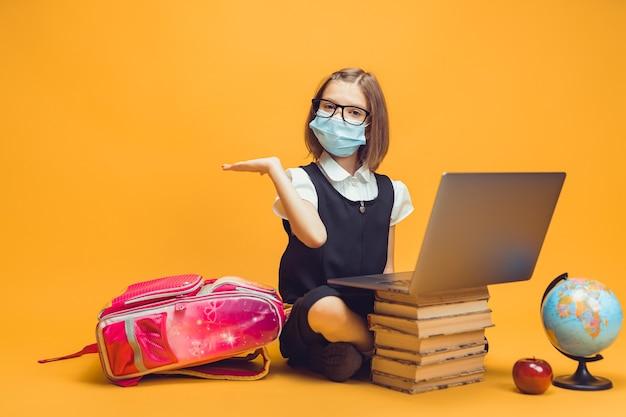 Uczeń w masce medycznej siedzi za stosem książek, a laptop wskazuje pustą przestrzeń edukacji dzieci