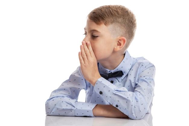 Uczeń w niebieskiej koszuli mówi szeptem z ręką przy ustach. na białym tle na białej ścianie. miejsce na tekst.