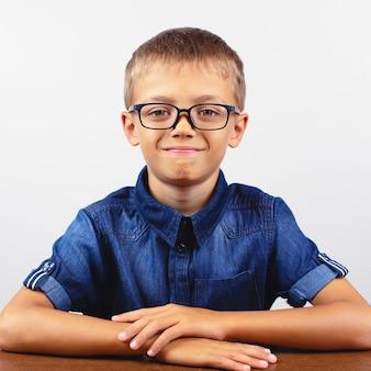 Uczeń w niebieskiej koszuli siedzi przy stole. chłopiec z okularami