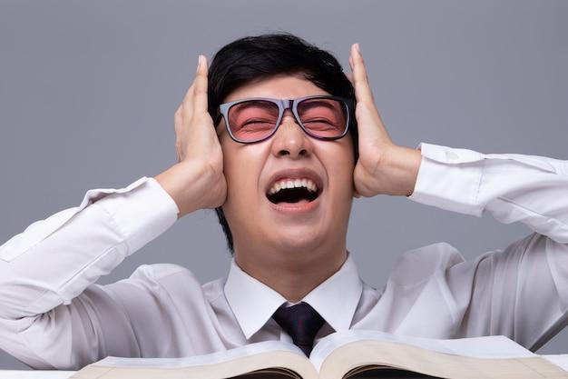Uczeń w okularach odczuwa stres podczas czytania książki