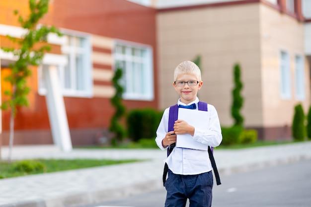 Uczeń w okularach z plecakiem i białą książką stoi przy szkole