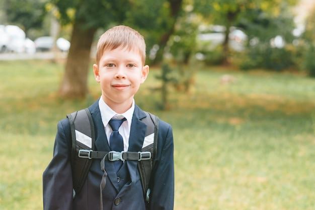 Uczeń w szkolnym mundurku i plecaku stoi na ulicy chłopiec w szkolnym mundurku