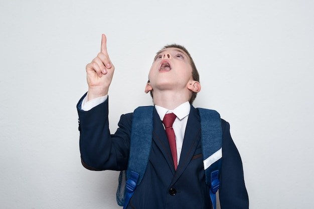 Uczeń w szkolnym mundurku pokazuje palec wskazujący w górę. chłopiec patrzy w górę. biały. edukacja dzieci.