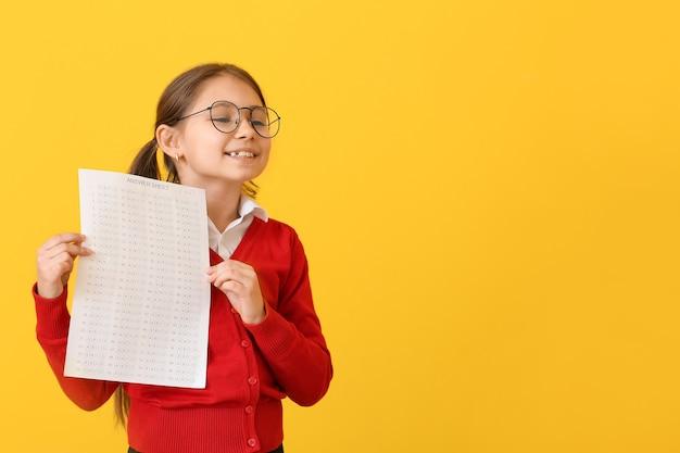 Uczeń z arkuszem odpowiedzi do testu szkolnego na żółto