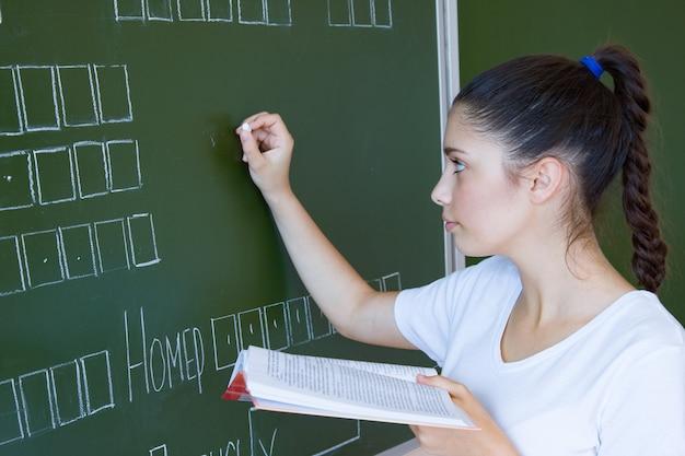 Uczeń z książką zostaje blisko blackboard w sala lekcyjnej