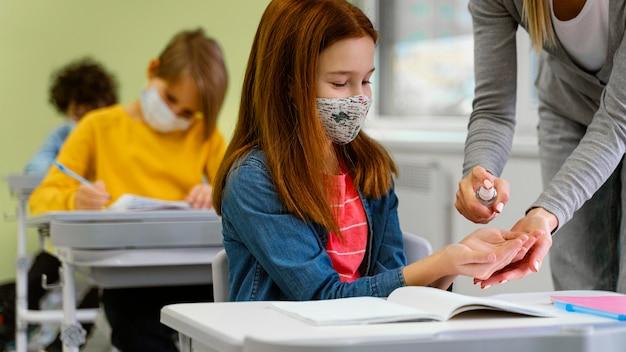 Uczeń z maską medyczną otrzymuje od nauczyciela środek dezynfekujący do rąk